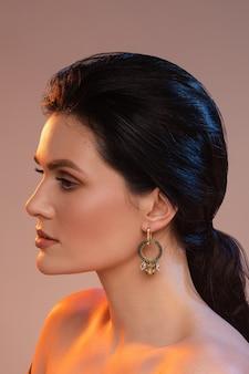 Bijoux élégants féminins. jeune femme brune avec boucle d'oreille, maquillage parfait sur une peau saine, gros plan portrait.