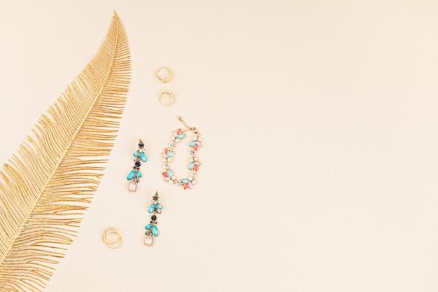 Bijoux élégants pour femme avec feuille d'or sur mur en cuir beige. bijouterie en ligne, idées cadeaux, blog beaty, concept de look élégant. pose plate minimale