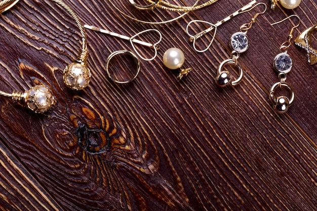 Les bijoux sur fond de bois, les bagues et les boucles d'oreilles dorées font un art cadeau chic d'être un bijoutier