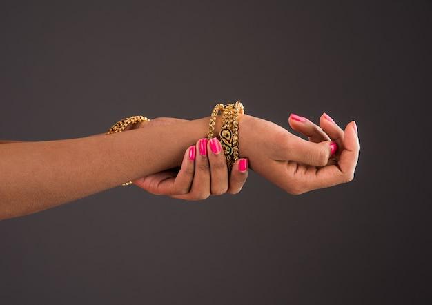 Bijoux indiens - gros plan d'une fille portant des bracelets ou des bracelets en or de créateurs traditionnels et montrant des poses de danse gracieuses de la main sur fond sombre, mise au point sélective