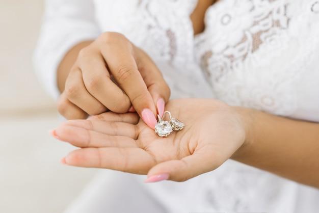 Bijoux de mariage pour femmes dans les mains de la mariée, mise au point sélective