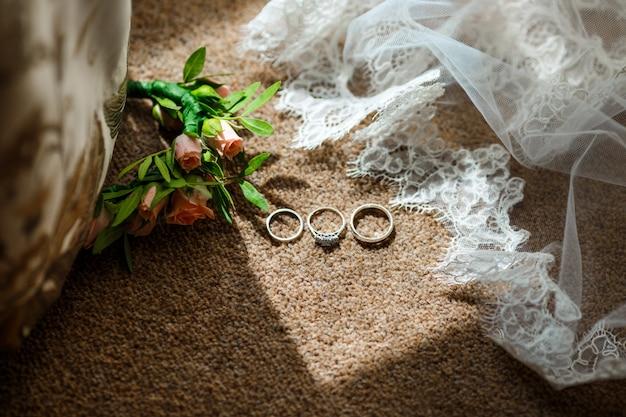 Bijoux de mariée couché près de voile avec dentelle et fleurs