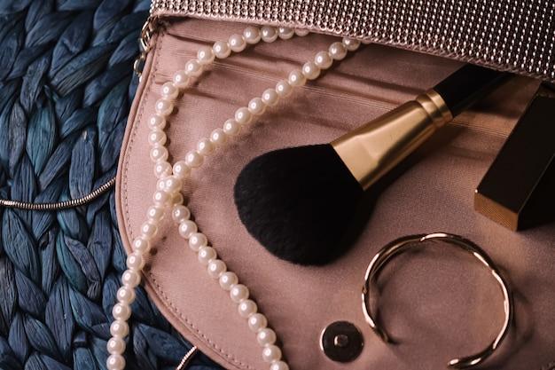 Bijoux et outils de maquillage à l'intérieur d'un sac à main de femme, beauté et mode gros plan