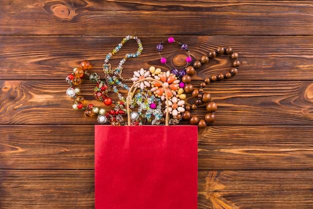 Bijoux en perles et sac en papier rouge sur fond en bois