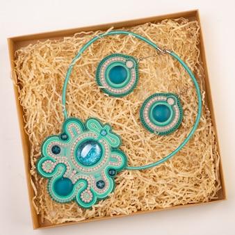 Les bijoux pour le cou se trouvent dans une boîte avec des copeaux