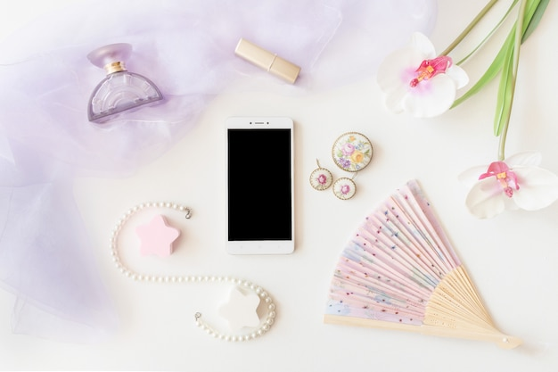 Bijoux de produits de beauté et vue de dessus de smartphone sur fond blanc.
