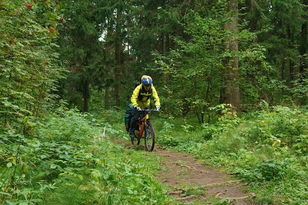 Bikepacker mâle monte sur un sentier dans la forêt de montagne d'automne