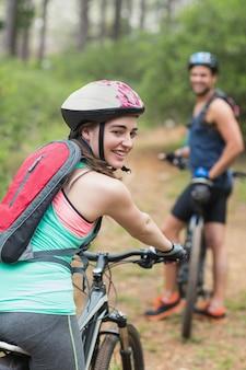 Biker femme heureuse avec l'homme sur le chemin de terre