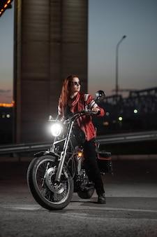 Biker fille posant sexuellement sur moto dans la ville de nuit