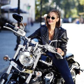 Biker girl dans une veste en cuir sur une moto