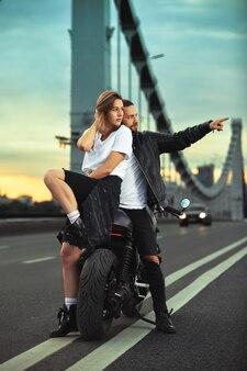 Biker homme et fille se tient sur la route et regarde au loin