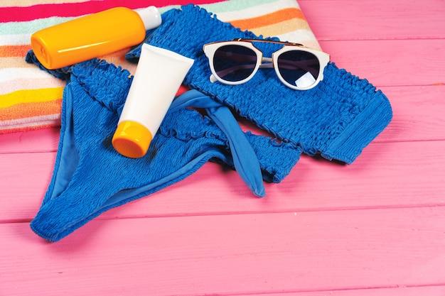 Bikini bleu avec bouteille de crème écran solaire sur fond de bois rose vif