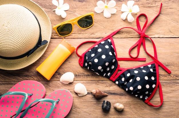 Bikini coloré de beauté et accessoires sur plancher en bois