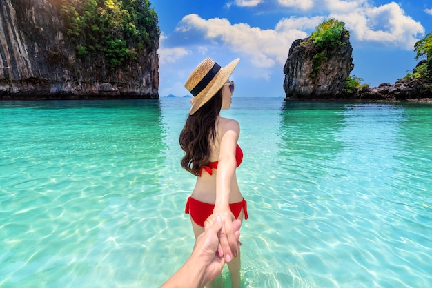 Bikini girl holding man's hand et le conduisant à l'île de koh hong à krabi, thaïlande