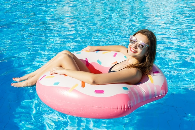 Bikini girl avec des lunettes de soleil détendue sur anneau de piscine gonflable rose