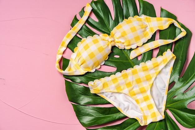 Bikini jaune avec feuille de monstera sur rose, pose plate