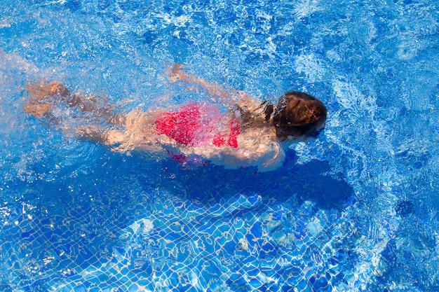 Bikini kid fille nageant sur la piscine de tuiles bleues