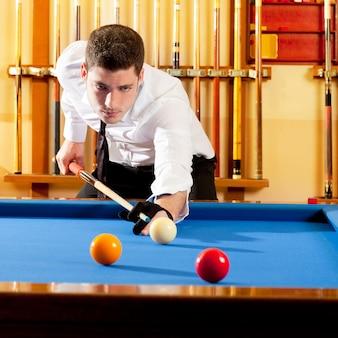 Billard gagnant bel homme jouant avec queue