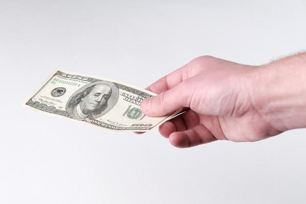 Un billet de 100 dollars qu'un homme tient et veut donner. shopping et corruption avec de l'argent liquide