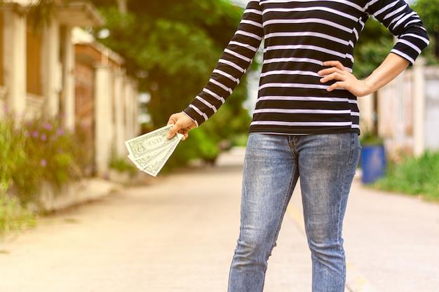 Billet de banque tenant la main d'une femme. achetez et économisez pour l'avenir.