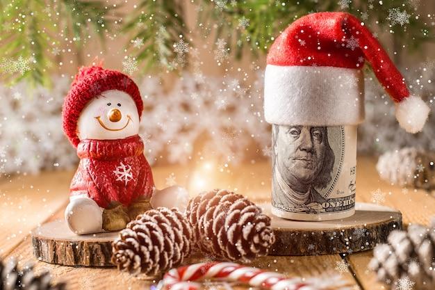 Billet de cent dollars avec bonhomme de neige dans un bonnet rouge