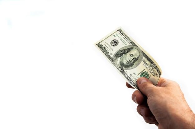 Un billet de cent dollars à la main sur fond blanc. isolé. un billet de cent dollars américains. une facture est en dollars. la main tend les dollars. place pour le logo, le lettrage, la mise en page, la mise en page.