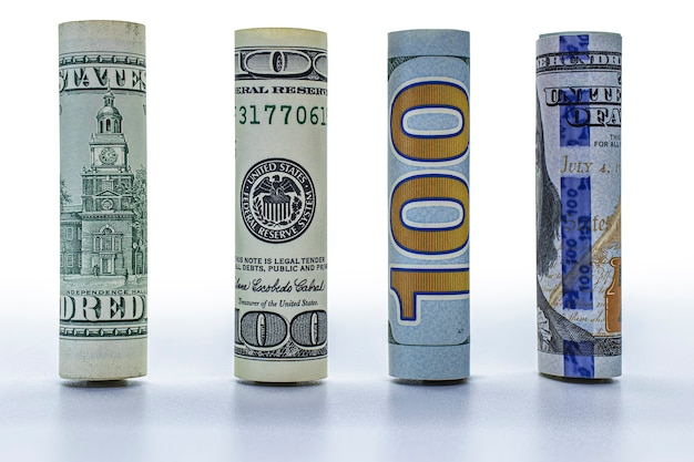 Billet de cent dollars roulé dans un tube. fermer. fond blanc isolé. concept pour le design.