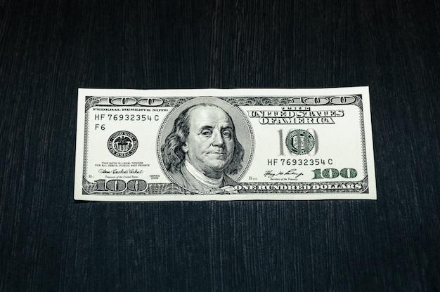 Un billet de cent dollars sur une table en bois texturé foncé.