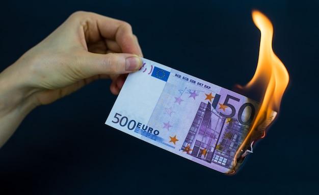 Un billet de cinq cents euros brûle sur fond noir.