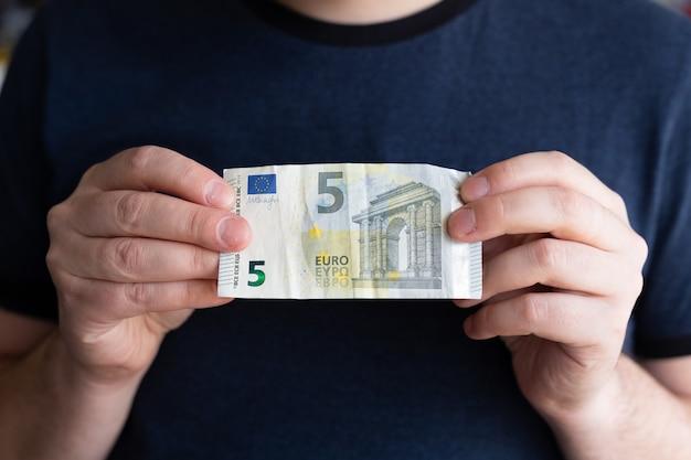 Billet de cinq euros. man main tenant de l'argent papier-monnaie. concept financier et monétaire. chercheur d'emploi. sans emploi.