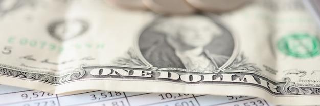 Un billet d'un dollar et des pièces de monnaie se trouvent sur le rapport financier