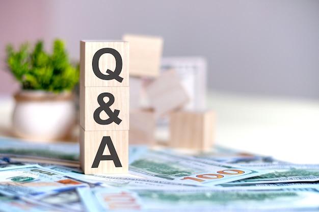 Billet de dollars avec calculatrice et mot q a. billets et cubes en bois avec lettres q et a. concept avec des blocs de bois et de l'argent.