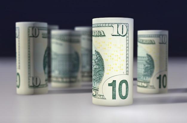 Le billet vert américain de 10 dollars roulé sur le noir