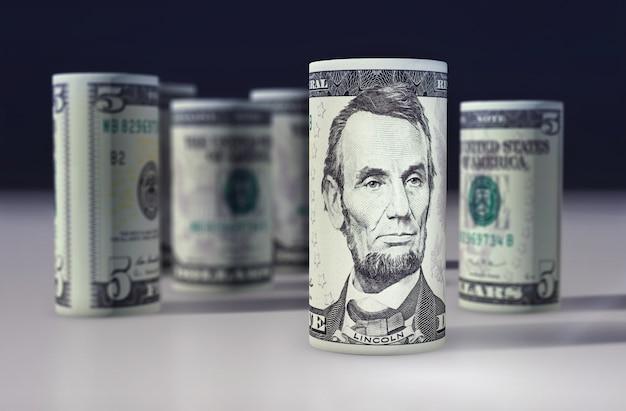 Le billet vert américain de 5 dollars roulé sur le noir