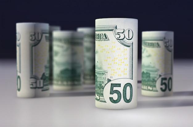 Le billet vert américain de 50 dollars roulé sur le noir