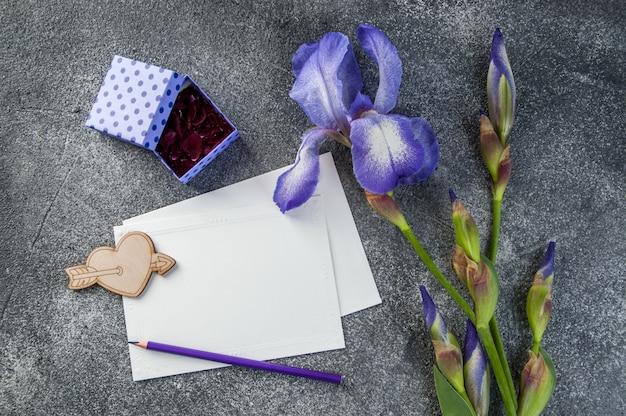 Billet vide, iris violet et coffret cadeau sur fond gris