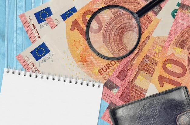 Billets de 10 euros et loupe avec sac à main noir et bloc-notes