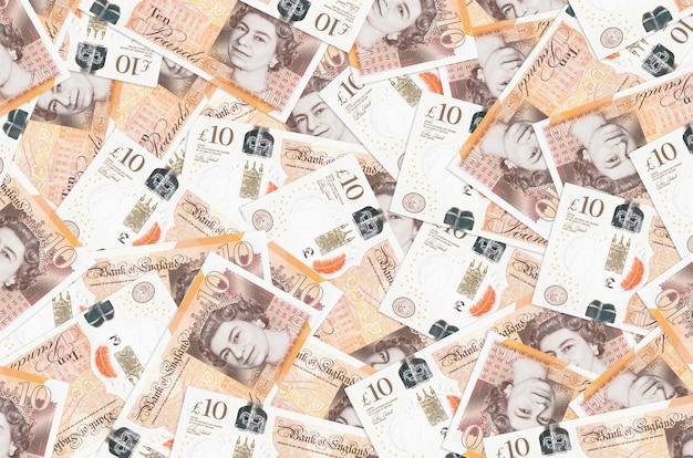 Les billets de 10 livres sterling se trouvent en gros tas. . une grosse somme d'argent