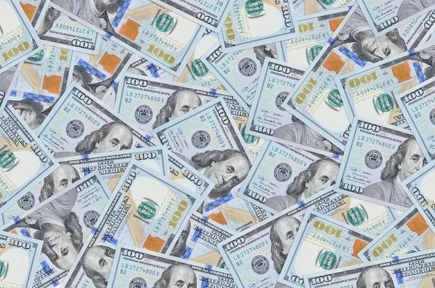 Les billets de 100 dollars américains se trouvent en gros tas. mur conceptuel de vie riche. une grosse somme d'argent
