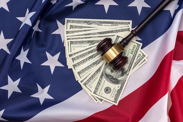 Des billets de 100 dollars et un marteau de juges placés sur le drapeau américain.