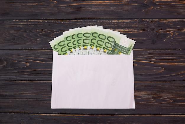 Billets de 100 euros dans une enveloppe blanche sur fond de bois