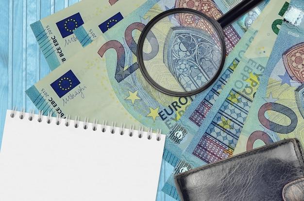 Billets de 20 euros et loupe avec sac à main noir et bloc-notes. concept de monnaie contrefaite. rechercher des différences dans les détails sur les factures d'argent pour détecter la fausse monnaie