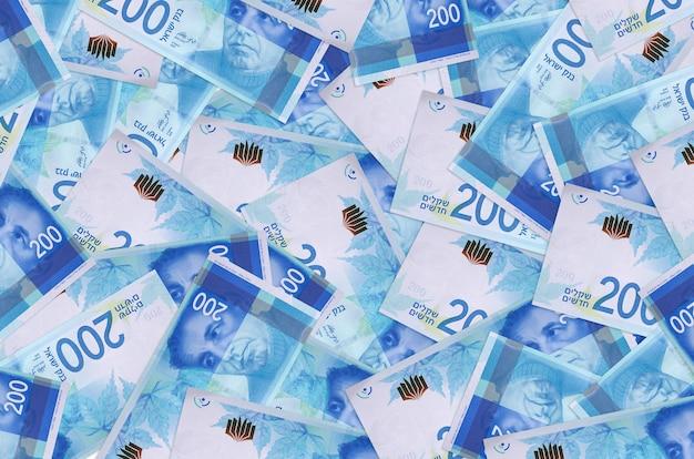 Les billets de 200 nouveaux shekels israéliens se trouvent en gros tas. mur conceptuel de vie riche. une grosse somme d'argent