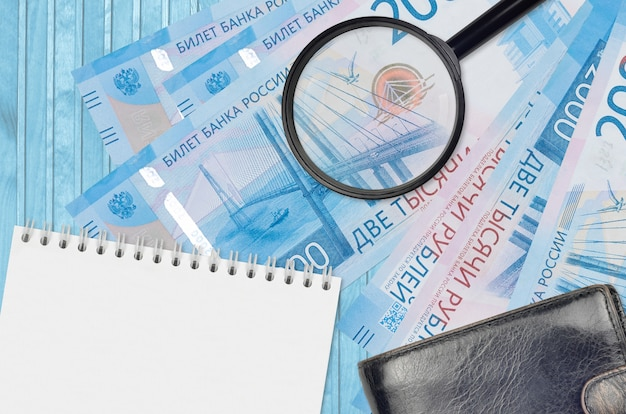 Billets de 2000 roubles russes et loupe avec sac à main noir et bloc-notes. concept de monnaie contrefaite. rechercher des différences dans les détails des factures d'argent pour détecter les faux