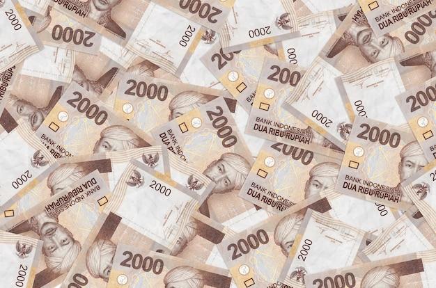 Les billets de 2000 roupies indonésiennes se trouvent en gros tas. . une grosse somme d'argent