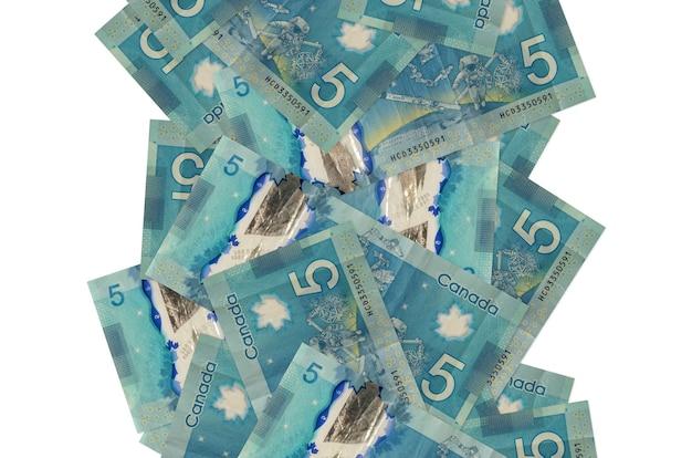 Billets de 5 dollars canadiens volant vers le bas isolés. de nombreux billets tombant avec espace copie blanche sur le côté gauche et droit
