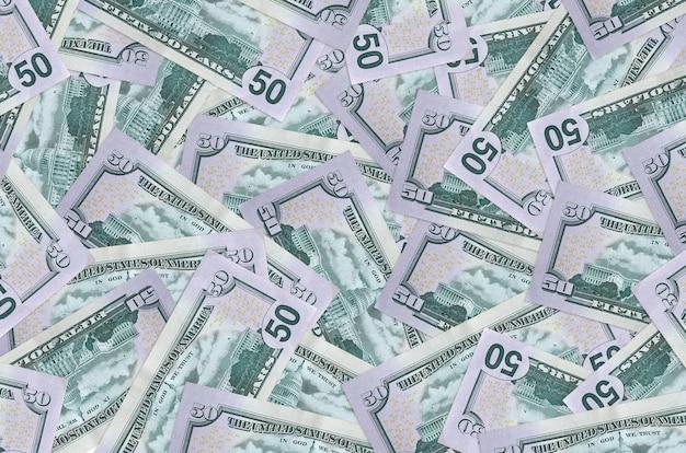 Les billets de 50 dollars américains se trouvent en gros tas. mur conceptuel de vie riche. une grosse somme d'argent