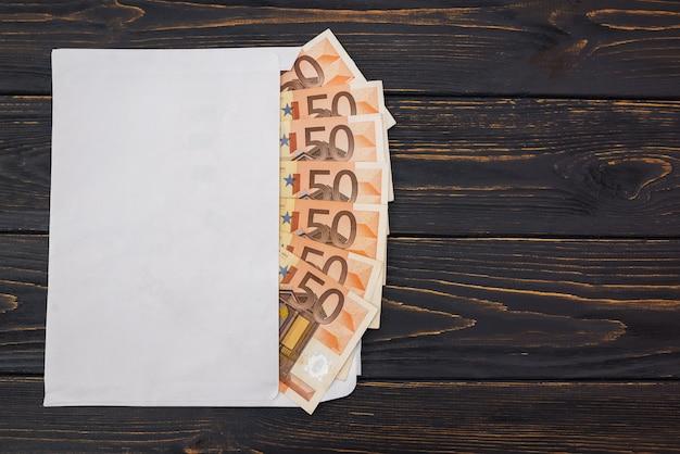 Billets de 50 euros dans une enveloppe blanche sur un fond en bois avec espace de copie.