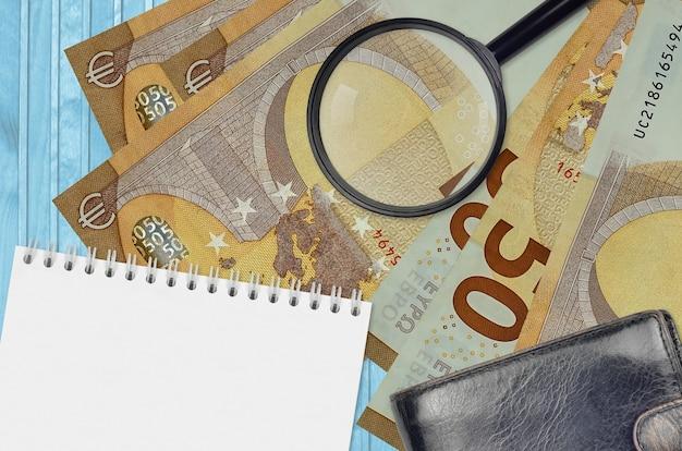Billets de 50 euros et loupe avec sac à main noir et bloc-notes