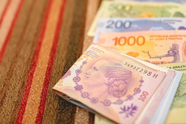 Billets d'argent argentin sur surface multicolore